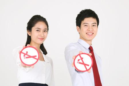 refusing: No smoking concept - Young Asian couple posing with no smoking sign