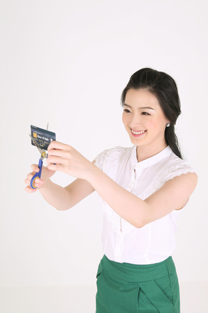 Shopping concept - Young Asian woman cutting her credit card with scissors