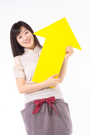 Young asian woman holding up an arrow sign in studio - isolated on white