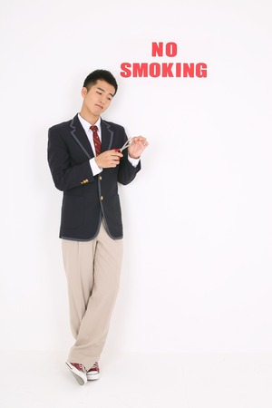 No smoking concept - Asian male student in school uniform cutting a cigarette in half with No smoking text on the wall