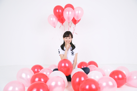 Party Concept - Young Asian woman posing with pink balloons, isolated on white