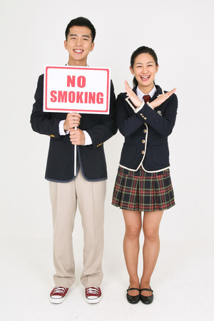 Not smoking concept - Étudiants asiatiques en uniforme scolaire posant avec des signes de non-fumeurs Banque d'images - 81428954