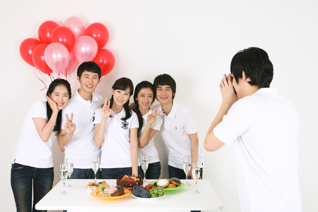 Party Concept - Young Asian people taking a photo, isolated on white