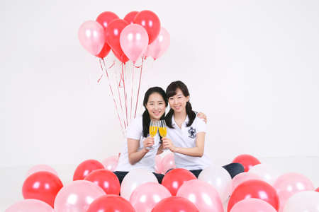 Party Concept - Two Young Asian women drinking champange with pink balloons, isolated on white