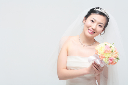 Beautiful Asian bride posing with bouquet, isolated on white