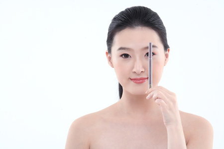 Beauty Concept - Young Asian woman applying make up with make up tools Stock Photo