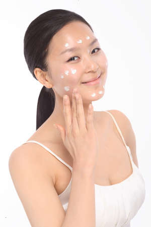Beauty Concept - Beautiful Asian woman applying moisturizer, isolated on white