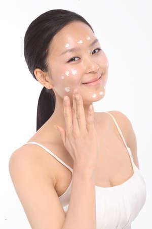cremas faciales: Concepto de belleza - hermosa mujer asiática aplicar crema hidratante, aislado en blanco