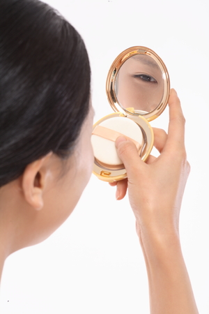 Beauty Concept - Beautiful Asian woman looking at mirror on compact pressed powder, isolated on white