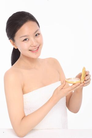 Beauty Concept - Beautiful Asian woman posing with compact pressed powder, isolated on white