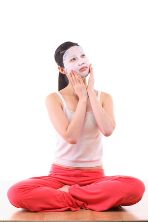 Beauty concept - Beautiful Asian woman with facial mask sheet on her face, isolated on white Stok Fotoğraf