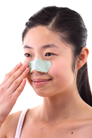 Beauty concept - Beautiful Asian woman with pore strip on her face, isolated on white