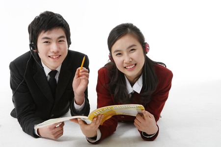 Two Asian girl and boy students laying down on the floor and reading a book together, isolated on white.