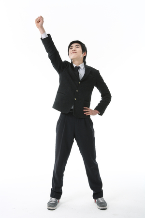 An Asian boy student posing in the studio, isolated on white. Stock Photo