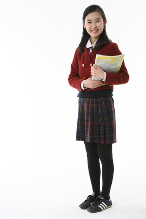 An Asian girl student holding a book with cheerful smile in the studio, isolated on white.