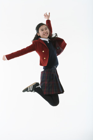 An Asian girl student student jumping in the studio, isolated on white.