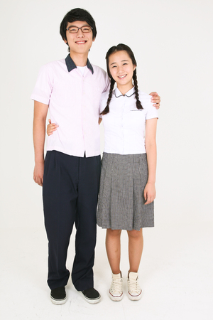Asian girl and boy standing together friendly and the boy putting his hand on her shoulder in the studio, isolated on white. Stock Photo
