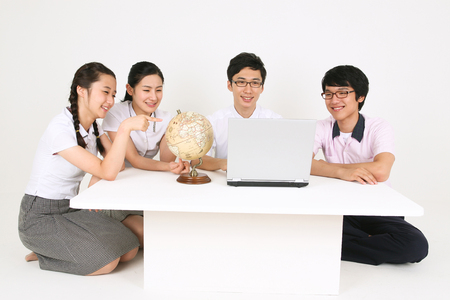 Three Asian students and a teacher sitting around the table and looking at the laptop in the studio, isolated on white. Stock fotó