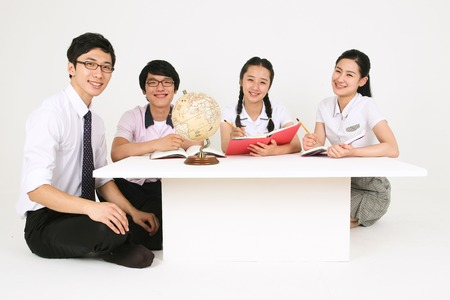 Three Asian students and a teacher sitting around the table and studying in the studio, isolated on white.