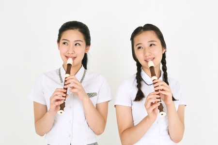 Two Asian girl students standing and playing a recorder in the studio, isolated on white Imagens