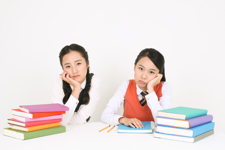 Two Asian girl students bored face sitting behind two stacks of books in the studio, isolated on white. Stock fotó