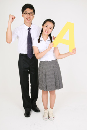 An Asian girl holding an alphabet sign with cute smile in ther studio and her teacher standing behind her in the studio, isolated on white