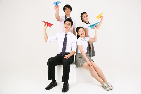 Three Asian students each holding a red arrow, baseball bet, laptop and their teacher holding a pot in the studio, isolated on white.