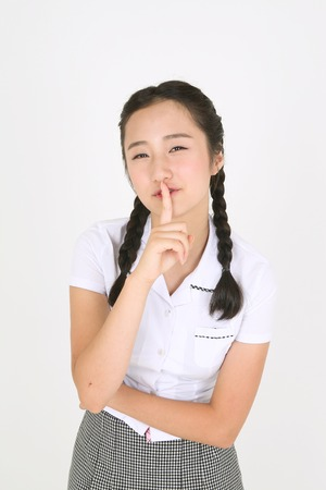 An Asian girl student trying to say quite with her finger in the studio, isolated on white.