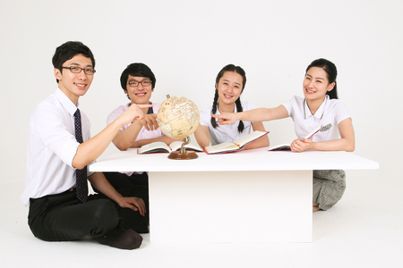 Three Asian students and a teacher sitting around the table and looking at a globe in the studio, isolated on white.