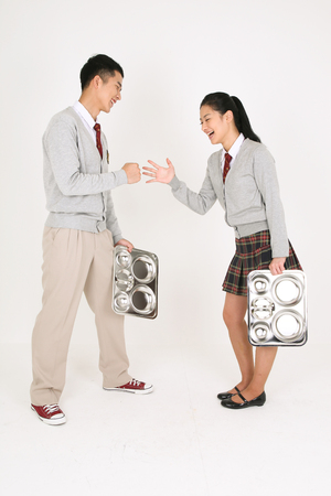An Asian girl and a boy students holding a food tray and doing rock paper scissors in the studio isolated on white.
