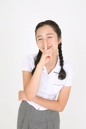 quite: An Asian girl student trying to say quite with her finger in the studio, isolated on white.