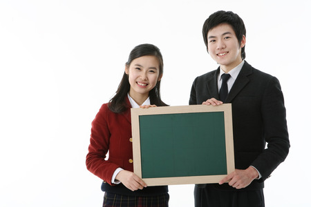 Two Asian girl and boy students holding a black board with smile in the studio, isolated on white. Stock Photo