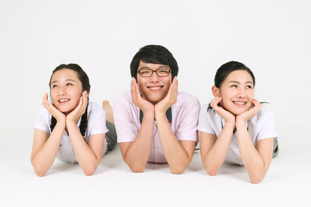 Two Asian girls and a boy students laying down on the floor and making cute face in the studio, isolated on white.