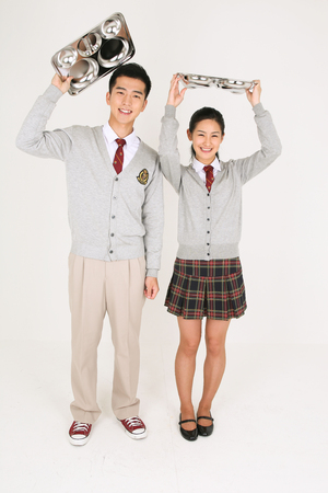 An Asian girl and a boy students holding a food tray and waiting for food in the studio isolated on white.