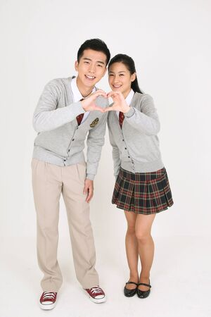 An Asian girl and a boy students standing friendly and they making heart gesture with their hands in the studio isolated on white. 写真素材