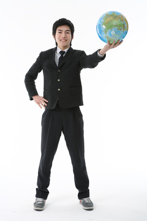 An Asian boy student holding a globe with cheerful smile in the studio, isolated on white. Stock Photo