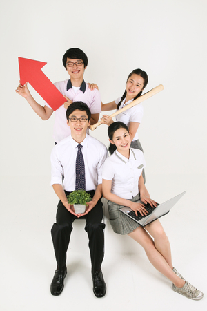 Three Asian students and their teacher holding a paper airplane in the studio, isolated on white.