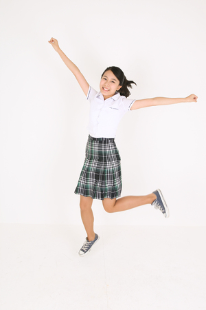 pleasantness: An Asian girl student jumping with her open arms in the studio, isolated on white.