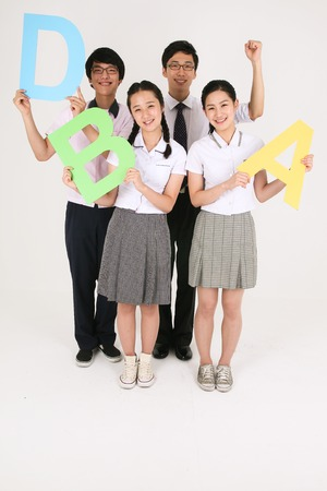 Three Asian students and their teacher standing together and holding alphabet sign with cheerful face in ther studio, isolated on white.
