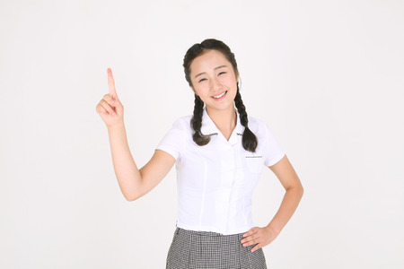nobleness: An Asian girl pointing up with her finger in the studio, isolated on white.