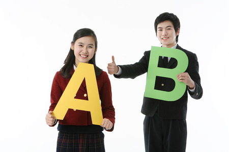Two Asian girl and boy students holding a alphabet sign with cheerful smile, isolated on white.