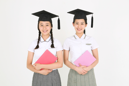 Two Asian girl students wearing a graduation hat and and holding a book in the studio, isolated on white