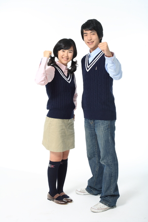 nobleness: Two Asian girl and boy standing and rasing their fist in the studio, isolated on white. Stock Photo