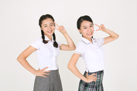 nobleness: Two Asian girl students standing together and making cute sign with their hands with lovely smile in the studio, isolated on white.