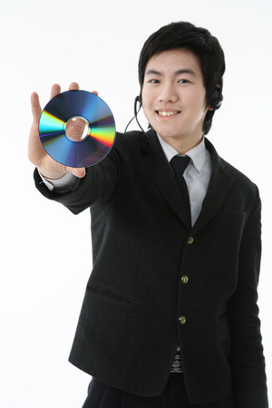 An Asian boy student holding a CD with cheerful smile in the studio, isolated on white.