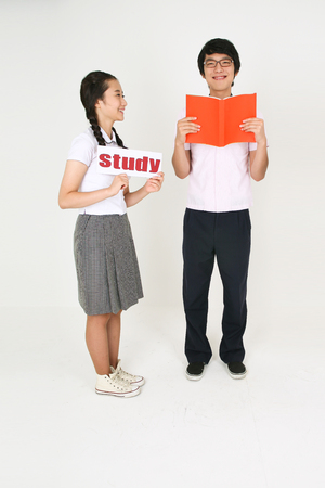 An Asian girl student holding a study sign and a boy student holding a book in the studio, isolated on white.
