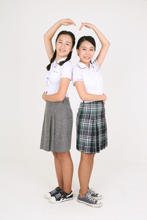 nobleness: Two Asian girl students standing back to back and making heart with their amrs with lovely smile in the studio, isolated on white.
