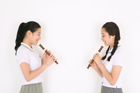 Two Asian girl students facing each other and they playing a recorder in the studio, isolated on white