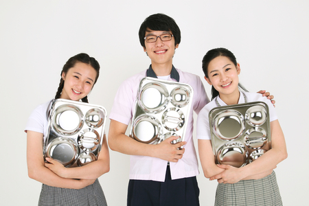 Two Asian girl students and a boy students holding a food tray in the studio, isolated on white.