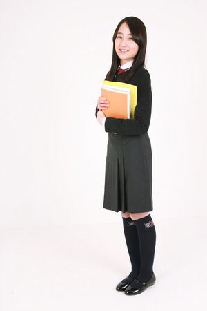 An Asian girl holding some books in her arms and staring at something in the studio, isolated on white. Stock Photo